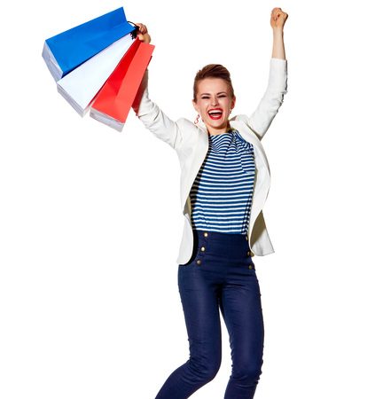 Shopping. The French way. Full length portrait of happy young woman with French flag colours shopping bags jumping against white background