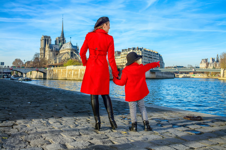Bright in Paris. Seen from behind stylish mother and daughter travellers in red coats on embankment near Notre Dame de Paris in Paris, France pointing at something Imagens