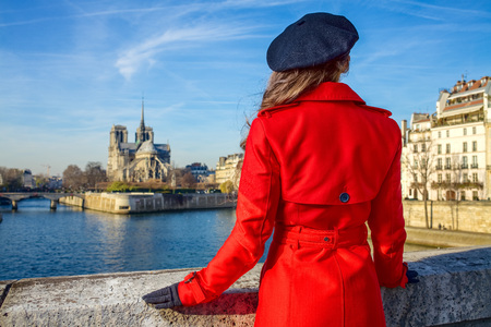 Bright in Paris. Seen from behind trendy woman in red trench coat on embankment near Notre Dame de Paris in Paris, France Stock Photo