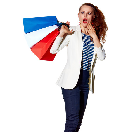 Shopping. The French way. Full length portrait of surprised young woman with French flag colours shopping bags on white background looking on copy space