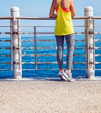 mp3 player: Look Good, Feel great! Closeup on young healthy woman in fitness outfit looking aside at the embankment