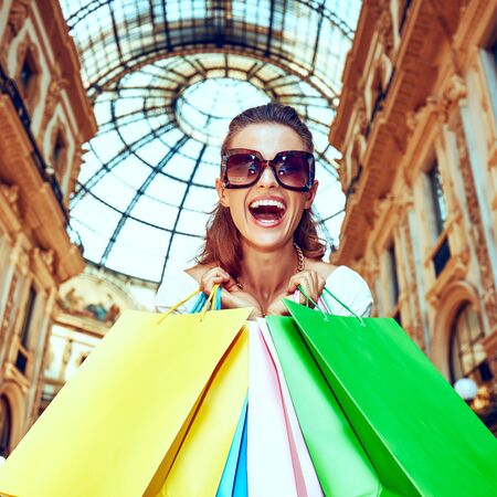 Discover most unexpected trends in Milan. Portrait of smiling fashion monger in eyeglasses with colorful shopping bags in Galleria Vittorio Emanuele II