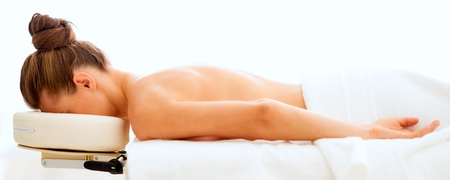 Relaxed young woman laying on massage table Stock Photo