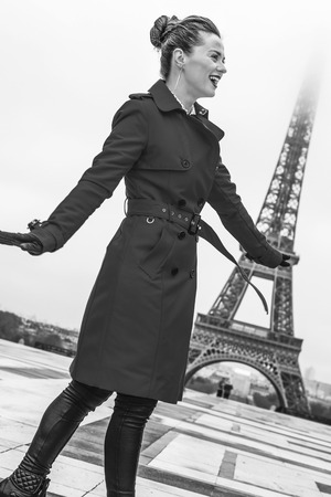 Bright in Paris. Full length portrait of smiling trendy woman in red trench coat in the front of Eiffel tower in Paris, France