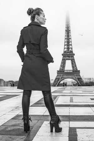Bright in Paris. Full length portrait of stylish woman in red trench coat against Eiffel tower in Paris, France looking into the distance