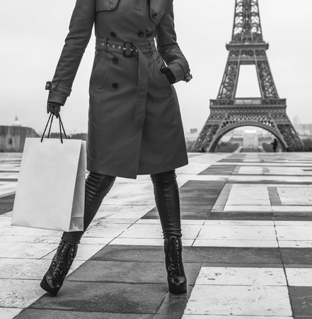 Bright in Paris. Closeup on stylish woman in red trench coat in Paris, France with shopping bag looking into the distance Stock Photo