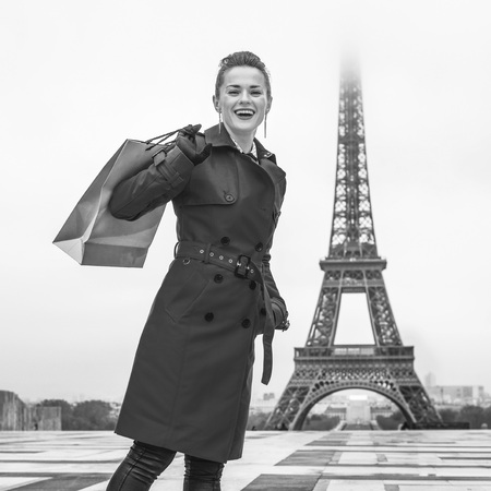Bright in Paris. Full length portrait of happy elegant woman in red trench coat against Eiffel tower in Paris, France with shopping bag