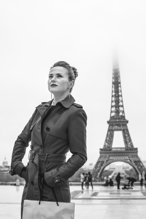 Bright in Paris. Portrait of modern woman in red trench coat against Eiffel tower in Paris, France with shopping bag looking into the distance Stock Photo