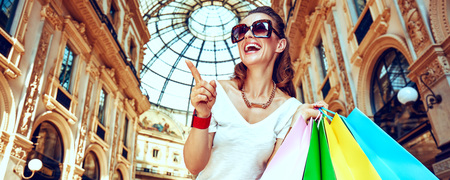 Discover most unexpected trends in Milan. Portrait of smiling fashion monger in eyeglasses with colorful shopping bags in Galleria Vittorio Emanuele II pointing on something Stok Fotoğraf