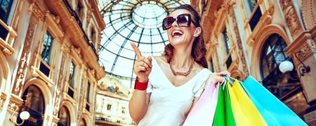 Ontdek de meest onverwachte trends in Milaan. Portret van glimlachende maniermonger in oogglazen met kleurrijke het winkelen zakken in Galleria Vittorio Emanuele II die op iets richten
