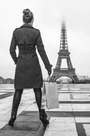 Bright in Paris. Seen from behind young woman in red trench coat against Eiffel tower in Paris, France with shopping bag