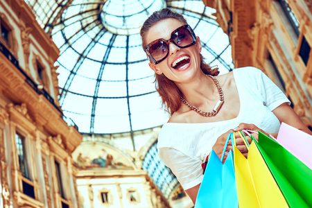 Discover most unexpected trends in Milan. smiling fashion monger in eyeglasses with colorful shopping bags in Galleria Vittorio Emanuele II Stock Photo