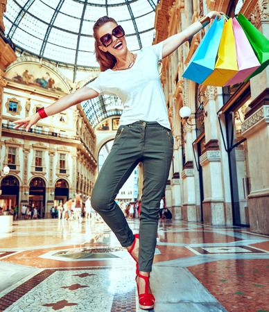 Discover most unexpected trends in Milan. Full length portrait of happy fashion monger in eyeglasses with colorful shopping bags having fun time in Galleria Vittorio Emanuele II Stock Photo