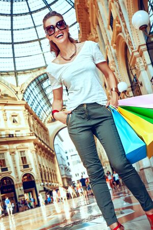 Discover most unexpected trends in Milan. smiling fashion woman in eyeglasses with colorful shopping bags in Galleria Vittorio Emanuele II