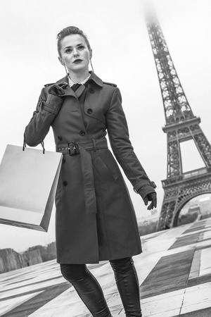 Bright in Paris. stylish woman in red trench coat in Paris, France with shopping bag looking into the distance