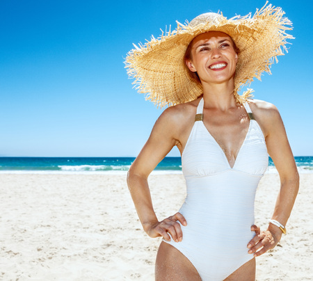 Heading to white sand blue sea paradise. Happy woman in white swimsuit and straw hat at sandy beach on a sunny day looking into the distance