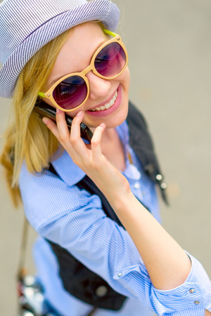 Young hipster talking cell phone on city street Stock Photo