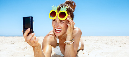 Heading to white sand blue sea paradise. Smiling woman in white swimsuit and funky pineapple glasses taking selfie at sandy beach on a sunny day
