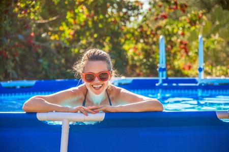 屋外で楽しい週末。サングラスのスイミング プールで青いビーチウェアで幸せな健康的な女性の肖像画 写真素材