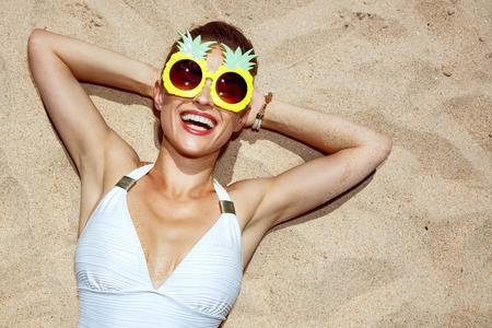 따뜻한 모래 치료. 수영복과 재미 파인애플 안경 모래에 누워 웃는 여자의 초상화