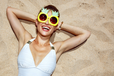 Warm sand treatment. Portrait of smiling woman in swimsuit and funny pineapple glasses laying on the sand Banco de Imagens