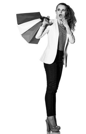 Einkaufen. Der französische Weg. Ganzaufnahme der überraschten jungen Frau mit französischer Flagge färbt Einkaufstaschen auf dem weißen Hintergrund, der auf Kopienraum schaut Standard-Bild - 75446224