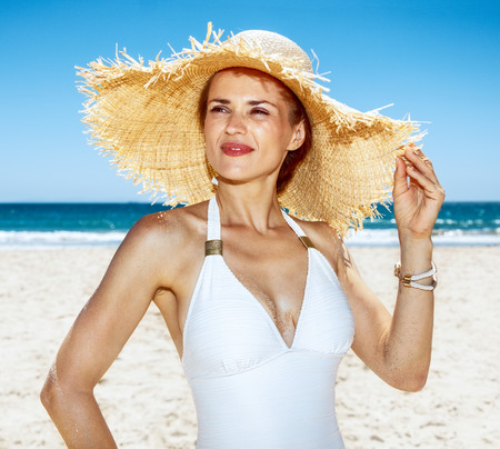 sunbath: Heading to white sand blue sea paradise. Portrait of woman in white swimsuit and straw hat at sandy beach on a sunny day looking into the distance