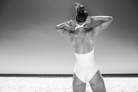 Heading to white sand blue sea paradise. Seen from behind woman tying white swimsuit at sandy beach on a sunny day