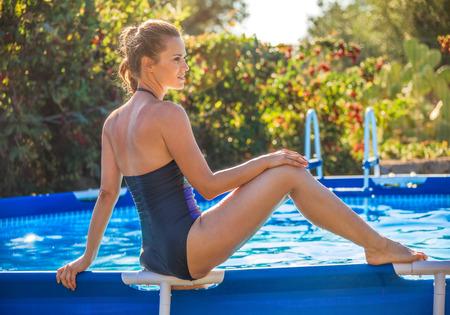 sitting on the ground: Fun weekend alfresco. healthy woman in blue beachwear sitting on the swimming pool Stock Photo