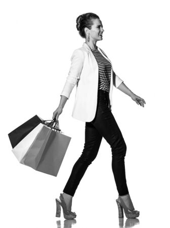 Shopping. The French way. Full length portrait of happy young woman with French flag colours shopping bags going to the side on white background Stock Photo