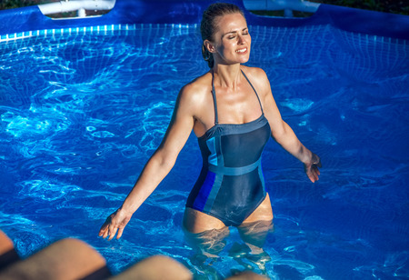 Fun weekend alfresco. relaxed healthy woman in blue swimwear standing in the swimming pool
