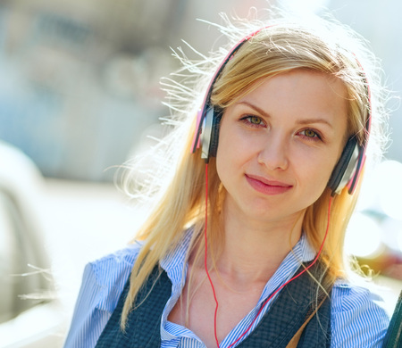 Portrait of happy girl listening music on city street