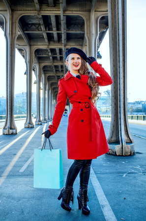 Bright in Paris. Full length portrait of smiling stylish traveller woman in red trench coat on Pont de Bir-Hakeim bridge in Paris with shopping bag looking into the distance Stock Photo