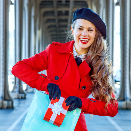 Bright in Paris. Portrait of happy young tourist woman in red trench coat on Pont de Bir-Hakeim bridge in Paris showing shopping bag and Christmas present box