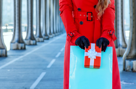 Bright in Paris. smiling trendy tourist woman in red trench coat on Pont de Bir-Hakeim bridge in Paris with shopping bag and Christmas present box Stock Photo