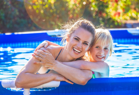 Fun weekend alfresco. Portrait of smiling active mother and child in swimwear in the swimming pool embracing