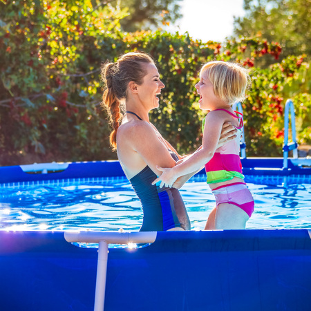 Fun weekend alfresco. happy healthy mother and child in swimsuit in the swimming pool playing