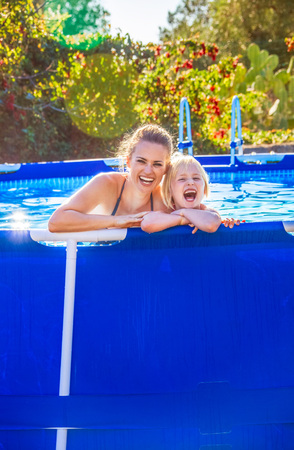 Fun weekend alfresco. Portrait of cheerful active mother and daughter in swimwear in the swimming pool