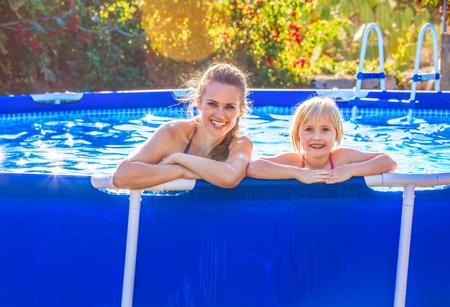 Fun weekend alfresco. Portrait of happy active mother and child in swimsuit in the swimming pool relaxing