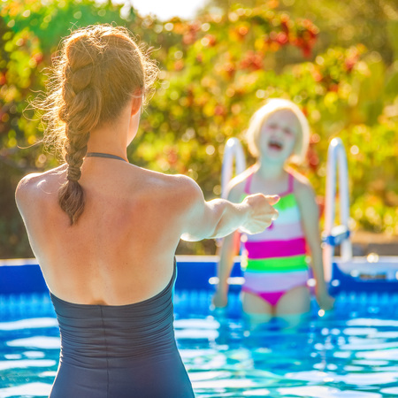mam: Fun weekend alfresco. smiling healthy mother and child in swimsuit in the swimming pool playing Stock Photo