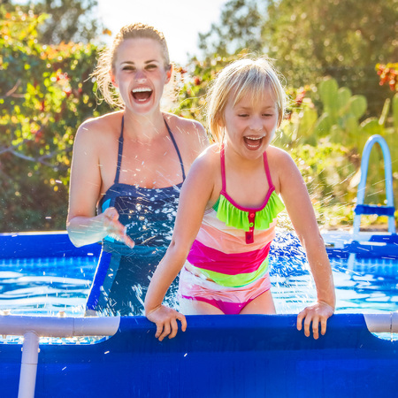 Fun weekend alfresco. cheerful healthy mother and daughter in swimsuit in the swimming pool playing