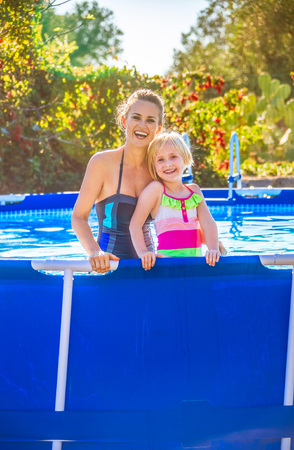 Fun weekend alfresco. Portrait of smiling active mother and daughter in swimwear in the swimming pool