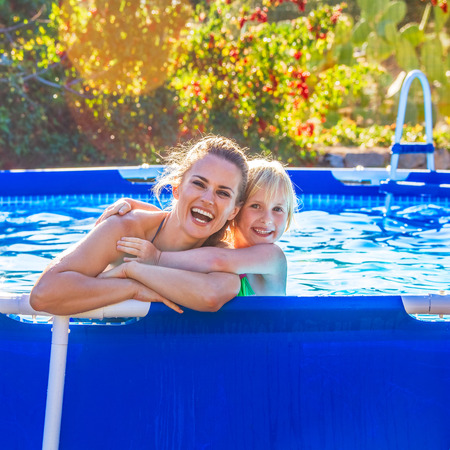 Fun weekend alfresco. happy active mother and child in beachwear in the swimming pool embracing Фото со стока