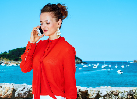 Luxury weekend retreat. smiling modern traveller woman in red blouse standing in front of the beautiful scenery overlooking lagoon with yachts in Donostia; San Sebastian, Spain talking on a mobile phone Stock Photo