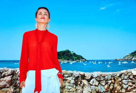 Luxury weekend retreat. Portrait of relaxed trendy tourist woman in red blouse standing in front of the beautiful scenery overlooking lagoon with yachts in Donostia; San Sebastian, Spain Stock Photo