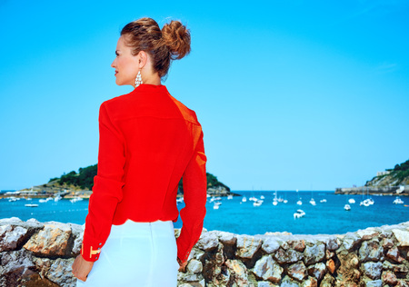 Luxury weekend retreat. Seen from behind traveller woman in red blouse standing in front of the beautiful scenery overlooking lagoon with yachts in Donostia; San Sebastian, Spain looking into distance