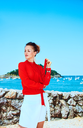 Luxury weekend retreat. pensive young woman in red blouse standing in front of the beautiful scenery overlooking lagoon with yachts in Donostia; San Sebastian, Spain looking aside