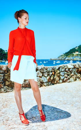 Luxury weekend retreat. Full length portrait of pensive stylish traveller woman in red blouse standing standing in front of the beautiful scenery overlooking lagoon with yachts in Donostia; San Sebastian, Spain