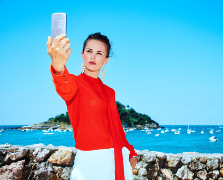 Luxury weekend retreat. stylish tourist woman in red blouse standing in front of the beautiful scenery overlooking lagoon with yachts in Donostia; San Sebastian, Spain with smartphone taking selfie