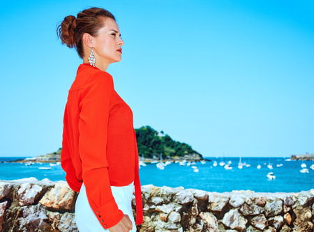 Luxury weekend retreat. stylish woman in red blouse standing in front of the beautiful scenery overlooking lagoon with yachts in Donostia; San Sebastian, Spain looking into the distance 版權商用圖片 - 75985368